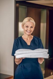 Obsługa hotelowa. uśmiechnięta blondynka w mundurze trzymająca czyste ręczniki