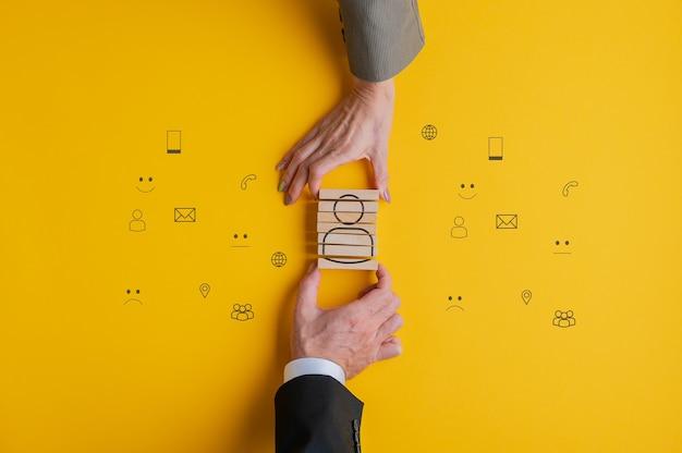 Obsługa klienta i wsparcie obraz koncepcyjny - ręce partnerów biznesowych montaż ikony ludzi na drewnianych klockach.