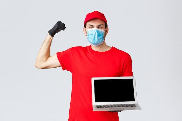 Obsługa klienta, paczki dostawy covid-19, koncepcja przetwarzania zamówień online. radujący się szczęśliwy kurier podniósł rękę tak, świętował, pokazując ekran laptopa, załóż maskę na twarz i rękawiczki