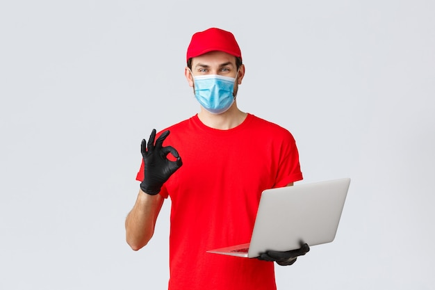 Obsługa klienta, paczki dostawy covid-19, koncepcja przetwarzania zamówień online. uśmiechnięty kurier w masce i rękawiczkach gwarantuje bezpieczeństwo przesyłki, realizację zamówienia, pokazuje znak porządku, trzyma laptopa