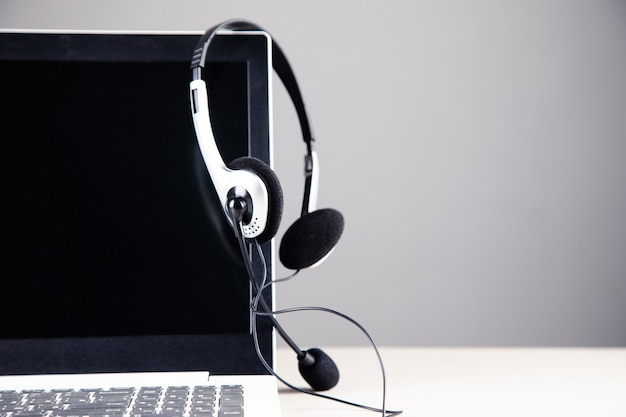 Obsługa komunikacji, zestaw słuchawkowy na klawiaturze laptopa.