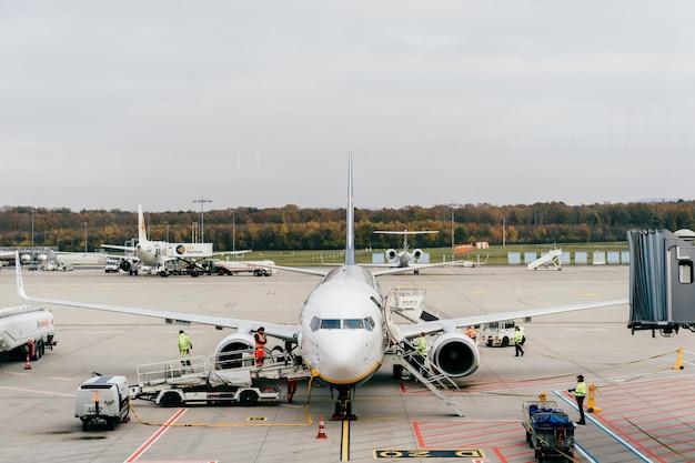 Obsługa lotniska koln bonn wylądował samolot. widok z poczekalni przez okno na pasie startowym z samolotem i personelem obsługi technicznej w trakcie pracy.