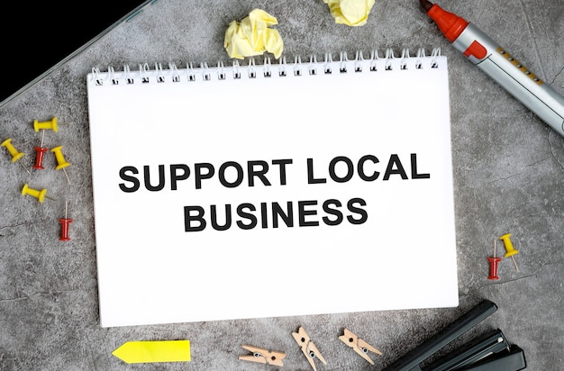 Obsługuj teksty lokalnych firm na białym notatniku za pomocą szpilek, markera i zszywacza na betonowym stole