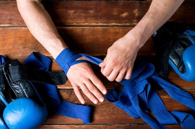 Obsługuje bandażową bokserską taśmę na jego rękach przed bokserskim dopasowaniem na drewnianej powierzchni. pojęcie treningu do treningu boksu lub walki. leżał płasko, widok z góry