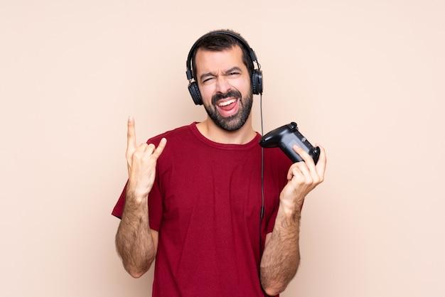 Obsługuje bawić się z wideo gry kontrolerem nad odosobnioną ścianą robi rockowemu gestowi