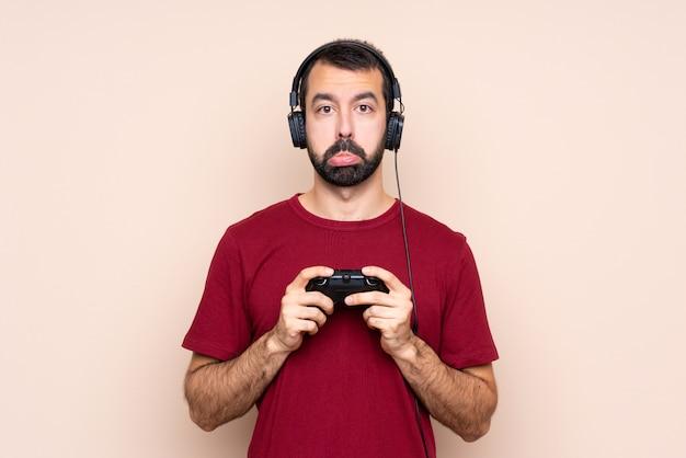 Obsługuje bawić się z wideo gry kontrolerem nad odosobnioną ścianą z smutnym i przygnębionym wyrażeniem