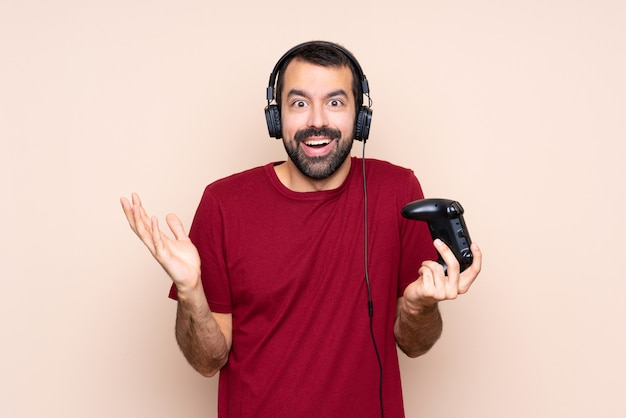 Obsługuje bawić się z wideo gry kontrolerem nad odosobnioną ścianą z zszokowanym wyrazem twarzy