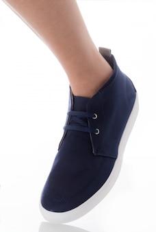 Obsługuje być ubranym błękitną mody obuwia pozycję z strona profilu widokiem odizolowywającym na bielu