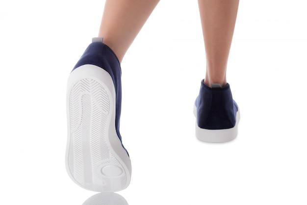 Obsługuje być ubranym błękitnego mody obuwia kroczenie od zadka widoku odizolowywającego na bielu