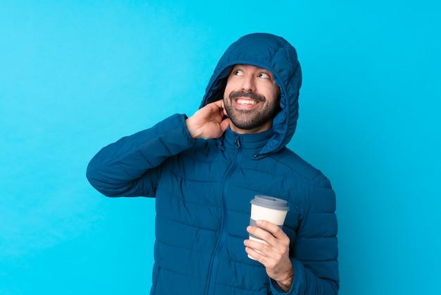 Obsługuje być ubranym zimową kurtkę i trzymać takeaway kawę nad odosobnioną błękit ścianą myśleć pomysł