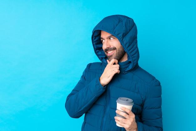 Obsługuje być ubranym zimową kurtkę i trzymać takeaway kawę nad odosobnioną błękit ścianą patrzeje strona