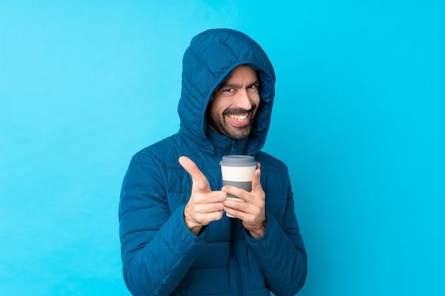 Obsługuje być ubranym zimową kurtkę i trzymać takeaway kawę nad odosobnioną błękit ścianą wskazuje przód i ono uśmiecha się