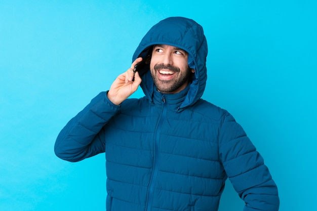 Obsługuje być ubranym zimową kurtkę i trzymać wynos kawę nad odosobnioną błękit ścianą utrzymuje rozmowę z telefonem komórkowym