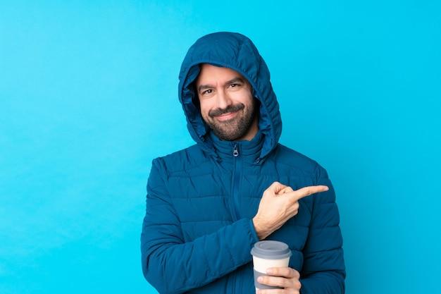 Obsługuje być ubranym zimową kurtkę i trzymać wynos kawę nad odosobnioną błękit ścianą wskazuje z boku przedstawiać produkt