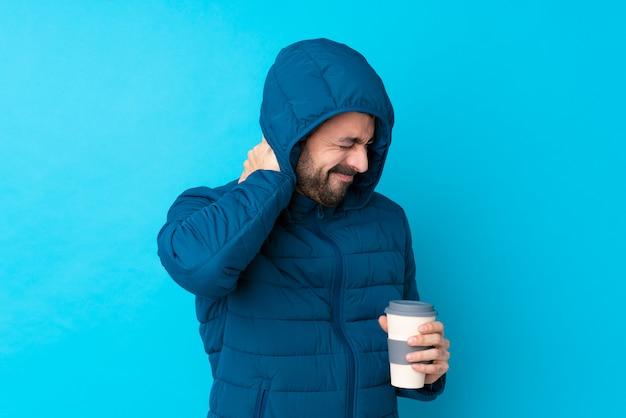 Obsługuje być ubranym zimową kurtkę i trzymać wynos kawę nad odosobnioną błękit ścianą z neckache