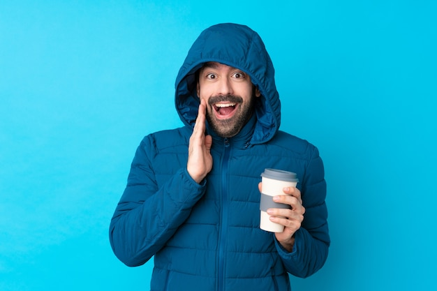 Obsługuje być ubranym zimową kurtkę i trzymać wynos kawę nad odosobnioną błękit ścianą z niespodzianką i zszokowanym wyrazem twarzy