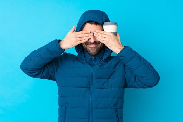 Obsługuje być ubranym zimową kurtkę i trzymać wynos kawę nad odosobnionym błękitnej ściany nakryciem ono przygląda się rękami