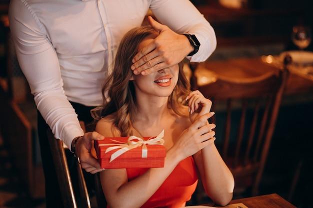 Obsługuje dawać prezenta pudełku na walentynka dniu przy restauracją