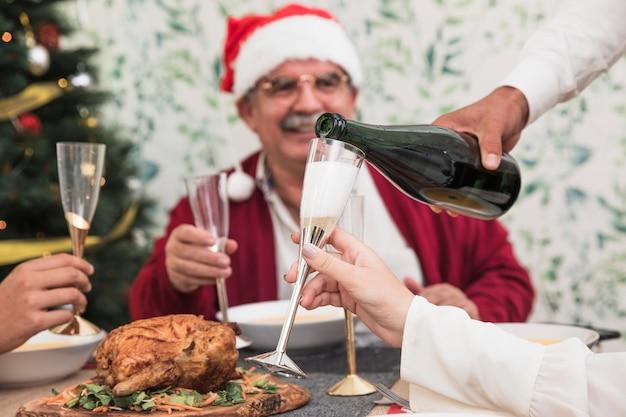 Obsługuje dolewanie szampana w szkle przy świątecznym stołem
