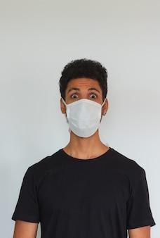 Obsługuje dorosłą czarną jest ubranym coronavirus maskę odizolowywającą na bielu