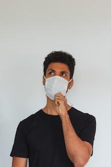 Obsługuje dorosłego czarnego jest ubranym coronavirus maski główkowanie odizolowywającego na bielu