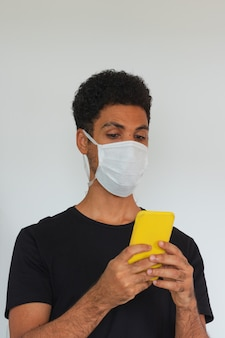 Obsługuje dorosłego czarnego jest ubranym coronavirus maski mienia telefon komórkowego odizolowywającego na bielu