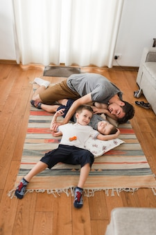 Obsługuje dosypianie z jego dwa synami na dywaniku w domu
