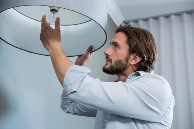 Obsługuje instalować żarówkę w żywym pokoju