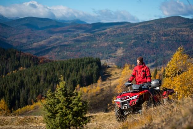Obsługuje jazdę na czerwonym atv na górskich drogach w pogodnym jesień dniu