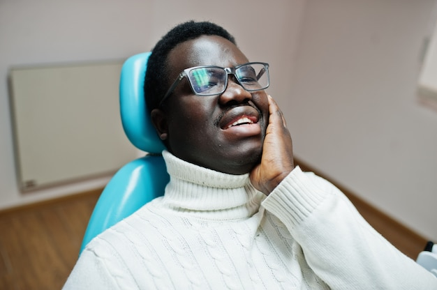 Obsługuje mieć bólu zęba obsiadanie w stomatologicznym krześle i potrzebuje pomagać, męski pacjent w bólu