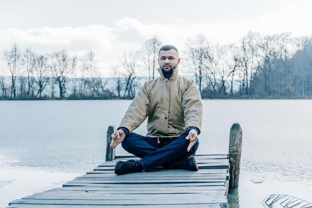 Obsługuje obsiadanie na starym drewnianym doku lub molu i patrzeć jeziornego horyzont. myślenie, relaksacja kontemplacji, koncentracja, pojęcie samotności.