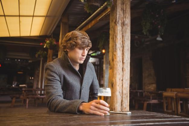 Obsługuje obsiadanie w barze z szkłem piwo na stole
