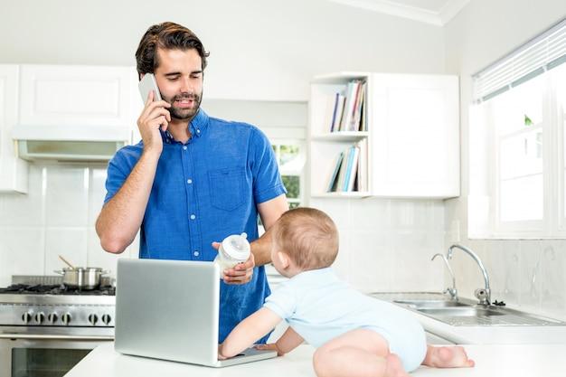 Obsługuje opowiadać na telefonie komórkowym podczas gdy karmiący syna przy stołem