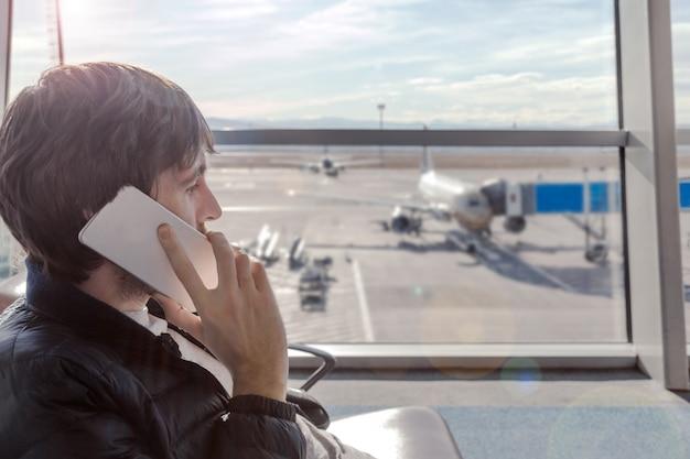 Obsługuje opowiadać telefonem komórkowym w lotniskowej sala podczas gdy cześć czeka wsiadać samolot.