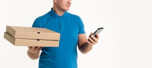 Obsługuje patrzeć smartphone podczas gdy trzymający pizz pudełka