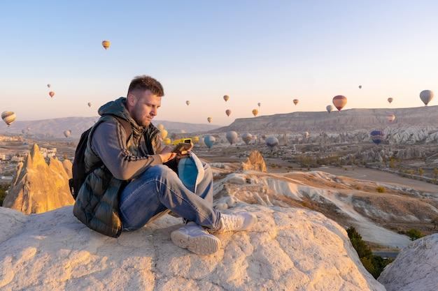 Obsługuje podróżnika ogląda gorące powietrze balony przy wzgórzem goreme z czarnym plecakiem, cappadocia, turcja.
