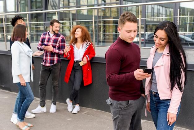 Obsługuje pokazywać smartphone jego żeński przyjaciel stoi blisko ich grupy przyjaciół