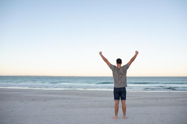 Obsługuje pozycję z rękami szeroko rozpościerać na plaży