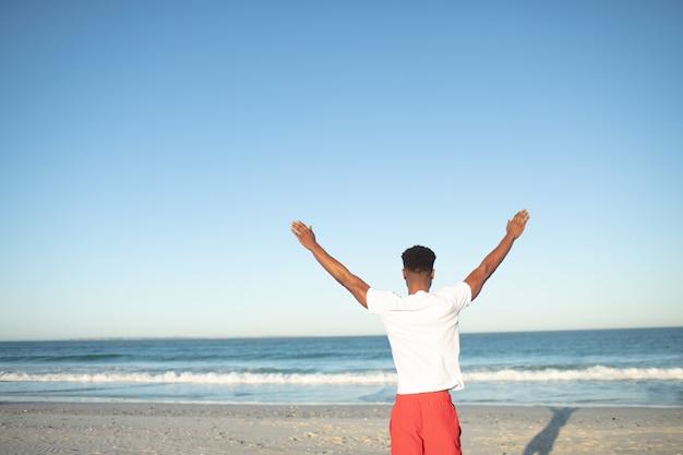 Obsługuje pozycję z rękami up na plaży
