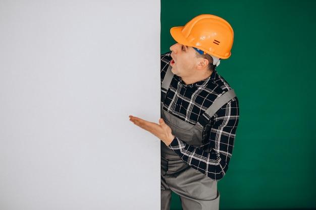 Obsługuje pracownika w ciężkim kapeluszu odizolowywającym na zieleni ścianie