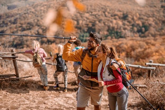 Obsługuje przytulenie kobiety i wskazuje z kijem przy ścieżką. kobieta trzyma mapę.
