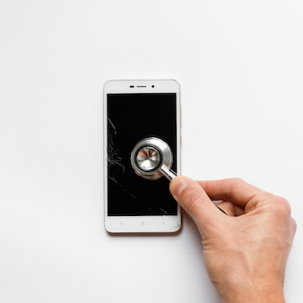 Obsługuje ręki mienia stetoskop na łamanym mobilnym smartphone po kropli, widok od above, na białym tle