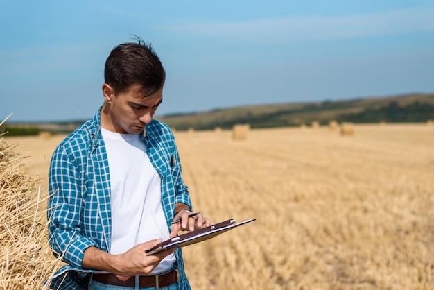 Obsługuje rolnika z pastylką w ręce, cajgami i koszula w polu, żniwo, sianokosy
