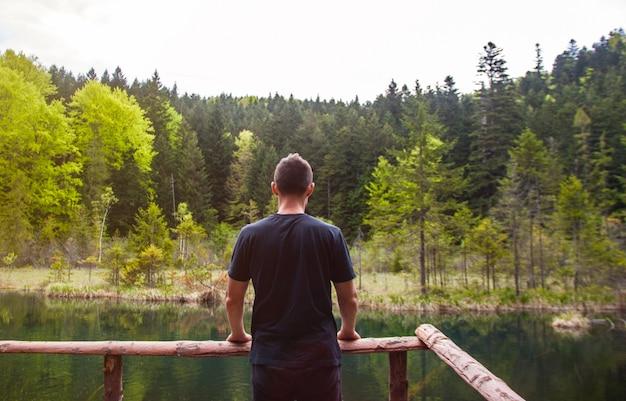 Obsługuje samotną pozycję i patrzeć na zdewastowanym jeziorze w lesie.