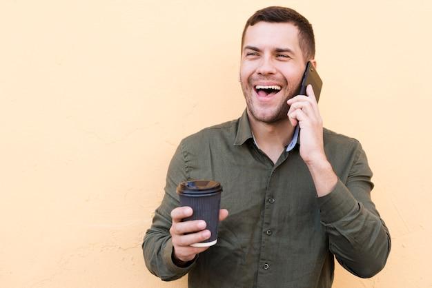 Obsługuje śmiać się na telefonie komórkowym z trzymać rozporządzalną filiżankę nad beżowym tłem