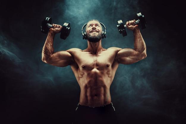 Obsługuje stażowych mięśnie z dumbbells w studiu na ciemnym tle z dymem.