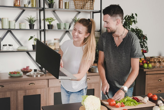 Obsługuje tnących warzywa z nożowym patrzeje kobiety mienia laptopem w kuchni