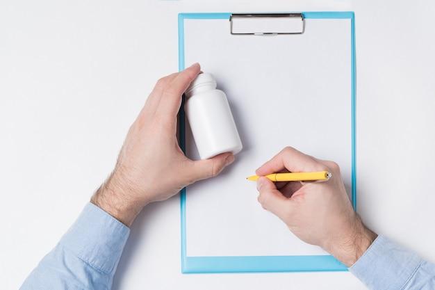 Obsługuje trzymać białego medycyny plastikowego pakunek dla pigułek i pisze na arkuszu. lekarz pisze pojęcie recepty. makieta