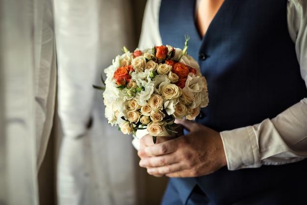 Obsługuje Trzymać Bridal Bukiet W Rękach, Fornal Przygotowywa W Ranku Przed ślubną Ceremonią Premium Zdjęcia
