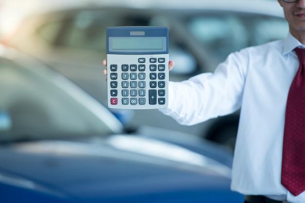 Obsługuje trzymać kalkulatora w samochodowej sala wystawowej, mężczyzna odciskania kalkulator dla biznesu finanse na samochodowej sala wystawowej rozmytym tle dla automobilowego lub transportu